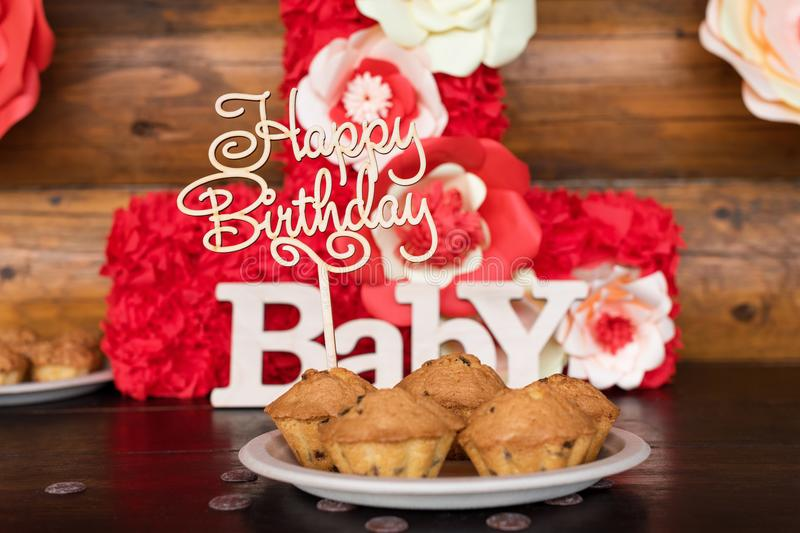Birthday cakes, muffins with wooden greeting signs on rustic background. Wooden sing with letters Happy Birthday, Baby. And holiday sweets stock photography