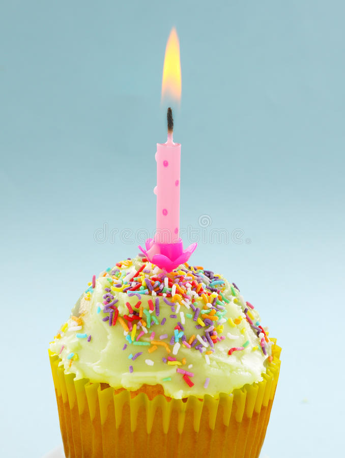 Birthday Candle Cup Cake. Cute single cup cake with a burning Birthday candle royalty free stock photography