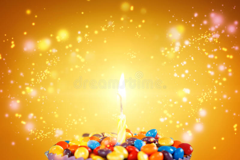 Birthday candle on Delicious cupcake with candies stock photo