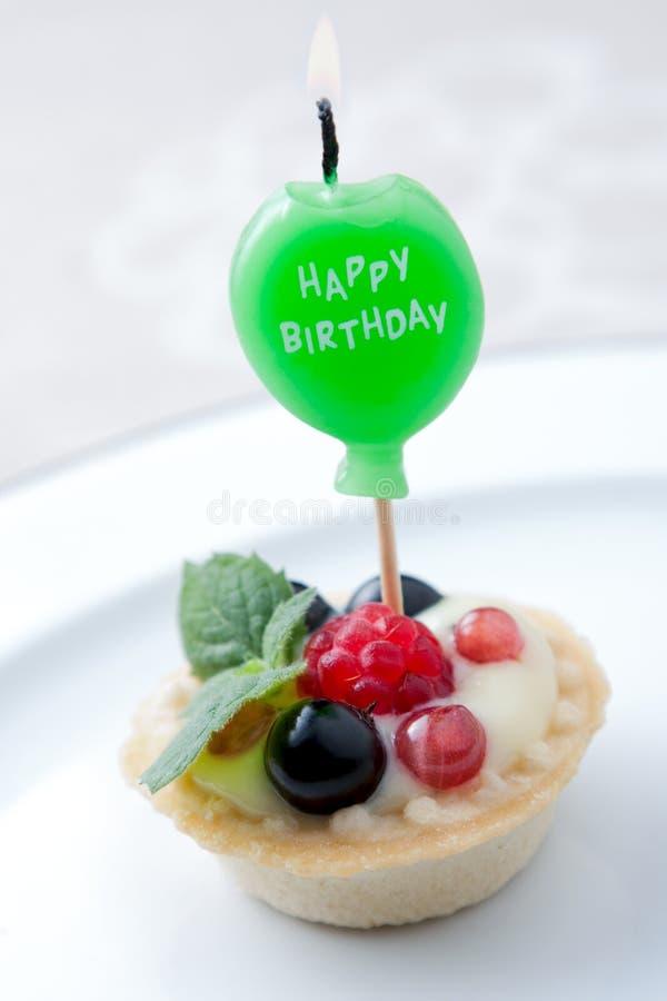 Birthday candle in fruit tart stock image