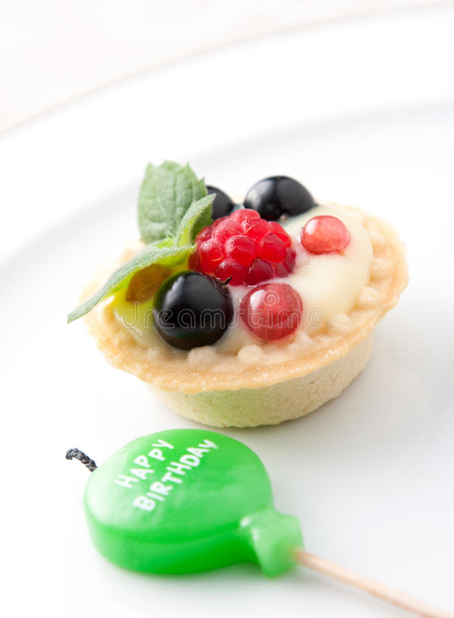 Birthday candle and fruit tart royalty free stock photo