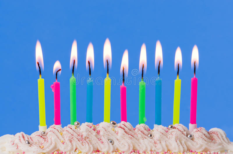 Birthday Candles. Lit birthday candles on decorated cake on blue background royalty free stock image