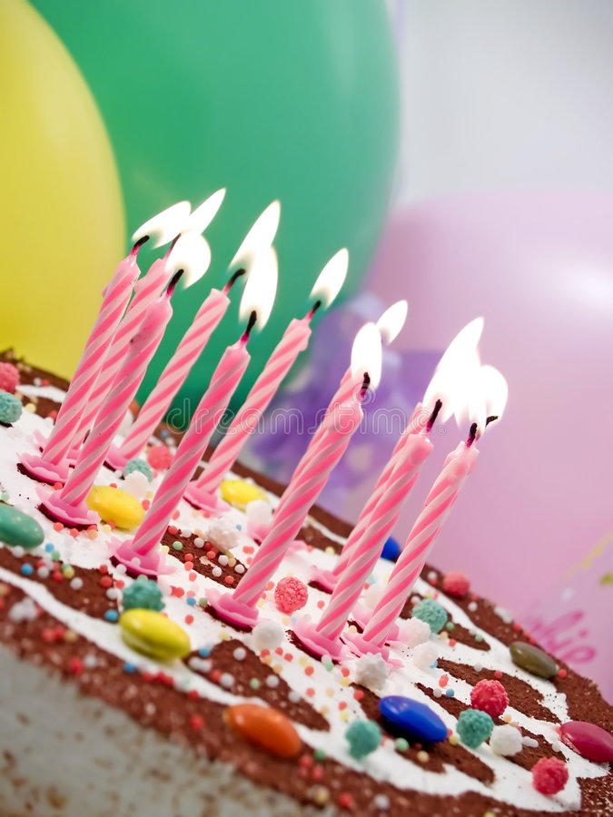 Birthday candles. Eleven burning candles at birthday cake, baloons at background royalty free stock images