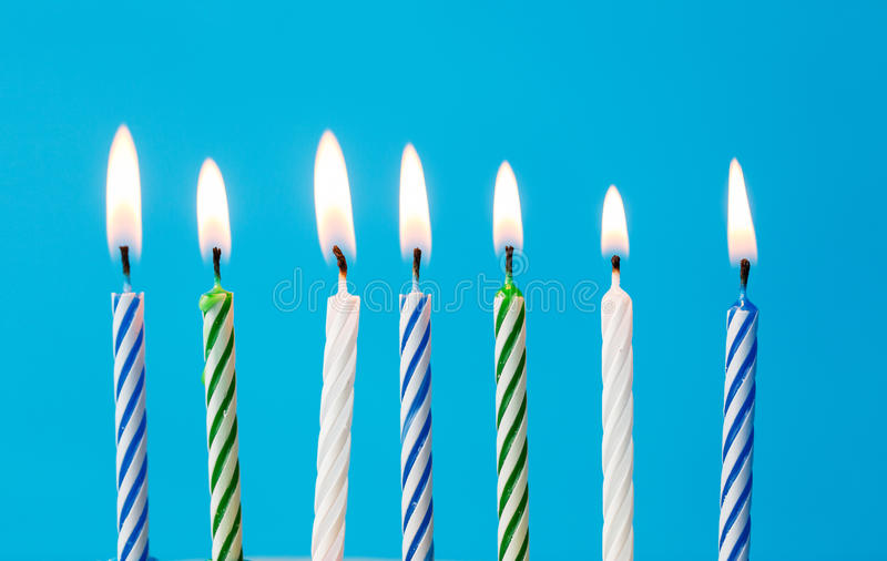 Birthday candles burning over blue background stock image