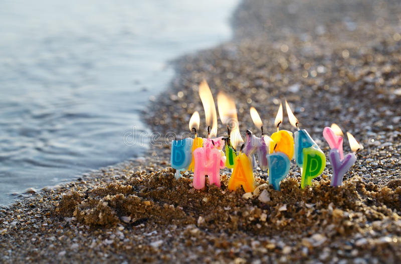 Birthday candles burning on a seashore royalty free stock photography