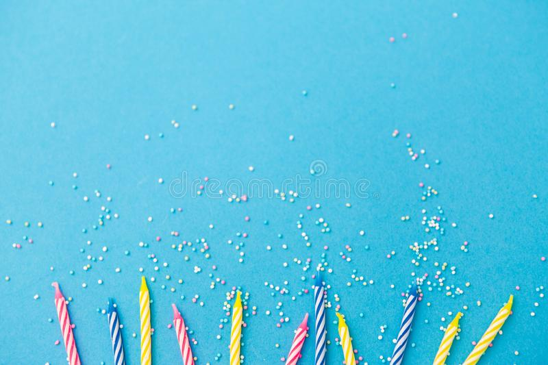Birthday candles with sprinkles on blue background. Holiday, celebration and party concept - birthday candles with sprinkles on blue background royalty free stock photos
