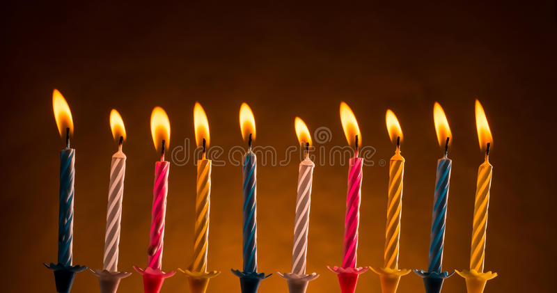 Birthday candles. Ten colorful illuminated birthday candles. Isolated over warm color background royalty free stock photography