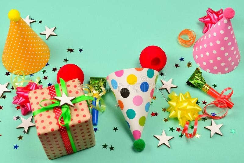 Birthday caps,  present, confetti, ribbons,  stars,  clown noses on a green background. Space for text or design royalty free stock images