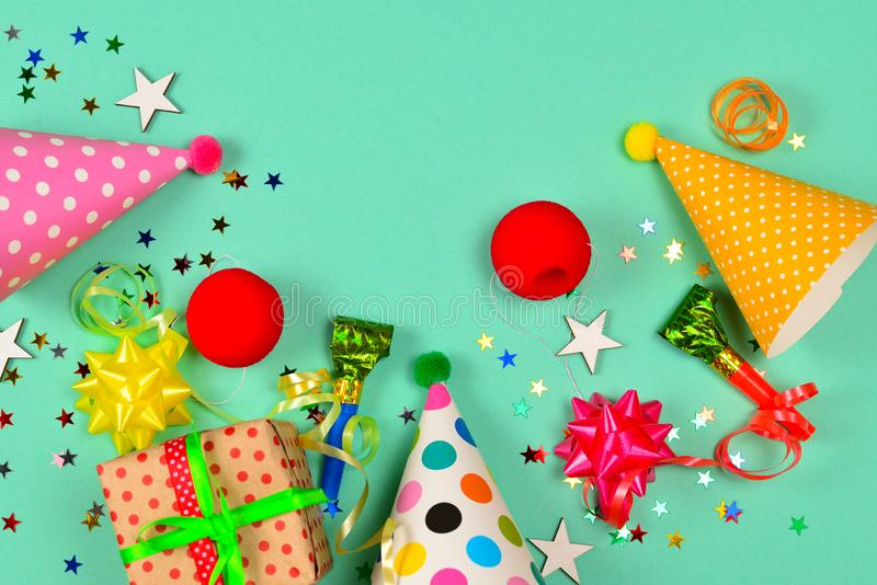 Birthday caps,  present, confetti, ribbons,  stars,  clown noses on a green background. Space for text or design royalty free stock photos