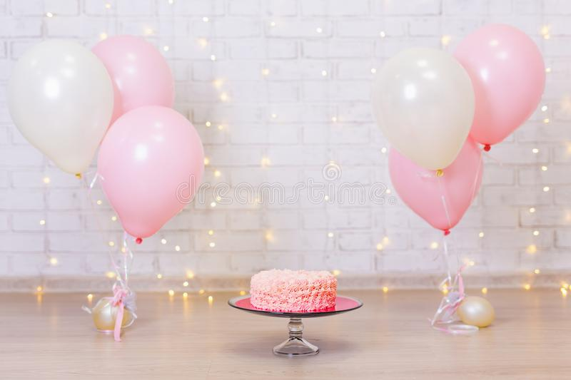 Birthday celebration background - cake over brick wall with lights and balloons. Birthday celebration background - cake over brick wall with lights and colorful stock photo