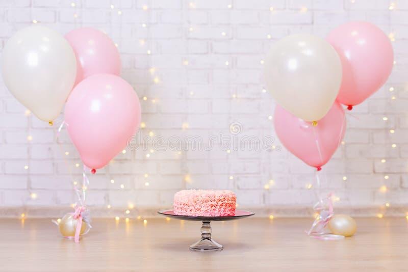 Birthday celebration background - pink cake over brick wall with. Birthday celebration background - pink cream cake over brick wall with lights and balloons stock photography