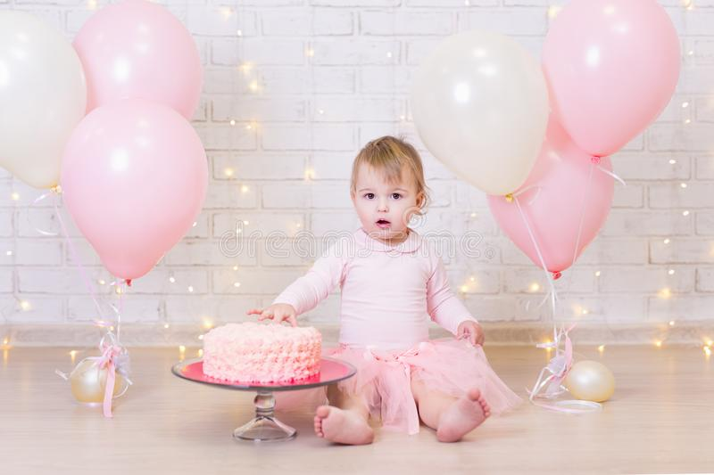 Birthday celebration - funny little girl with cake over brick wa. Ll background with lights and colorful balloons stock photography