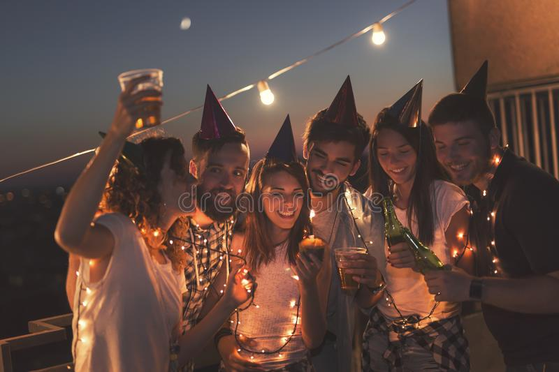 Birthday celebration. Group of young friends having a birthday party at a building rooftop, singing a song and blowing a candle. Focus on the birthday girl stock photos