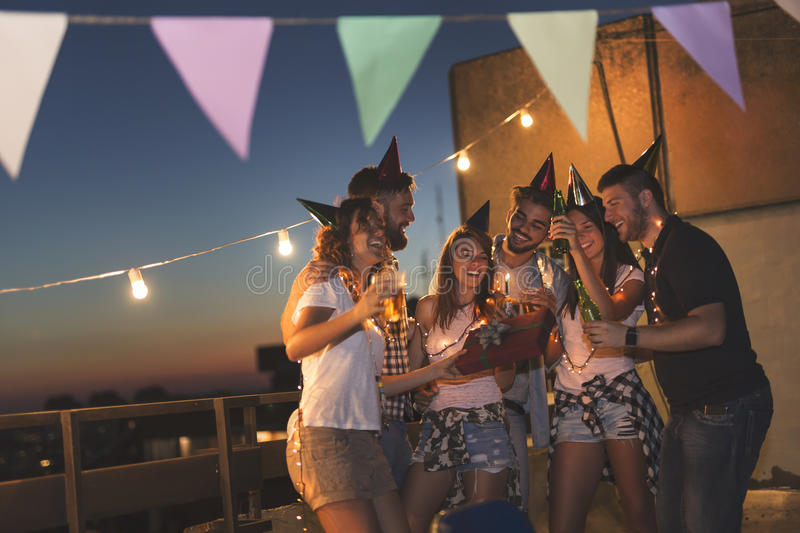 Birthday celebration. Group of young friends having a birthday party at a building rooftop, singing a song and blowing a candle. Focus on the people in the royalty free stock image