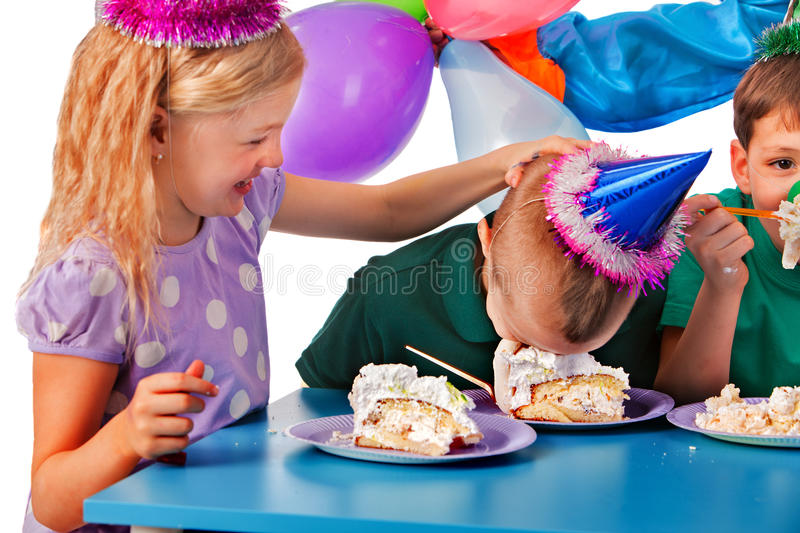 Birthday children celebrate party and eating cake on plate together . Portrait of three fun kids happy girl and boy in party hat and messy face have cake fight stock image