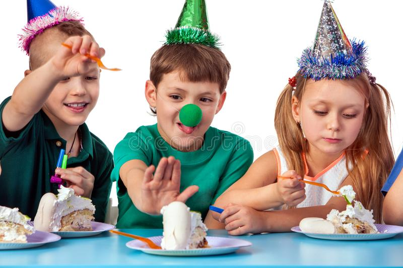 Birthday children celebrate party and eating cake on plate together. Portrait of three kids happy girl and boy with clown nose and party hat sitting for table stock photo