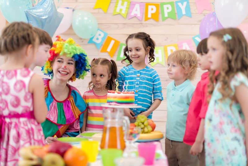 Birthday party. Kids with clown gathered around birthday cake royalty free stock photography