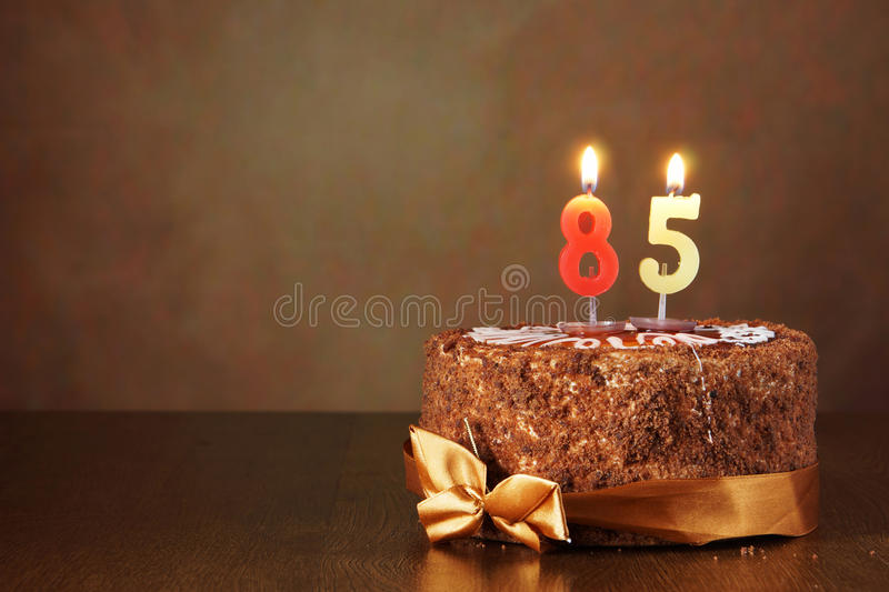 Birthday chocolate cake with burning candles as number eighty five. Birthday chocolate cake with burning candles as a number eighty five on brown background royalty free stock images