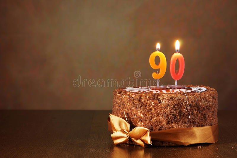 Birthday chocolate cake with burning candles as a number ninety. On brown background stock photography