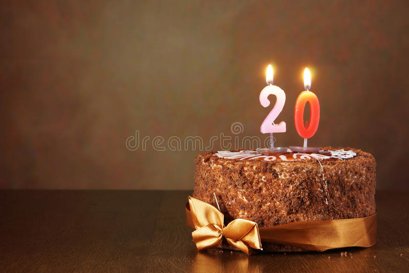 Birthday chocolate cake with burning candles as a number twenty. On brown background stock images