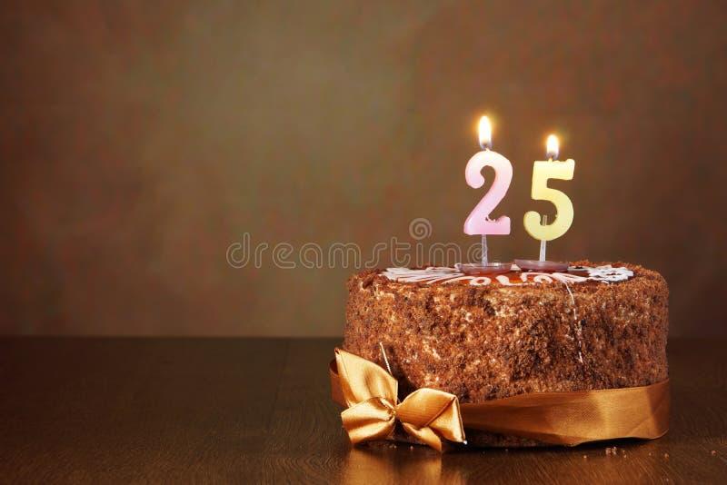Birthday chocolate cake with burning candles as number twenty five. Birthday chocolate cake with burning candles as a number twenty five on brown background royalty free stock photos