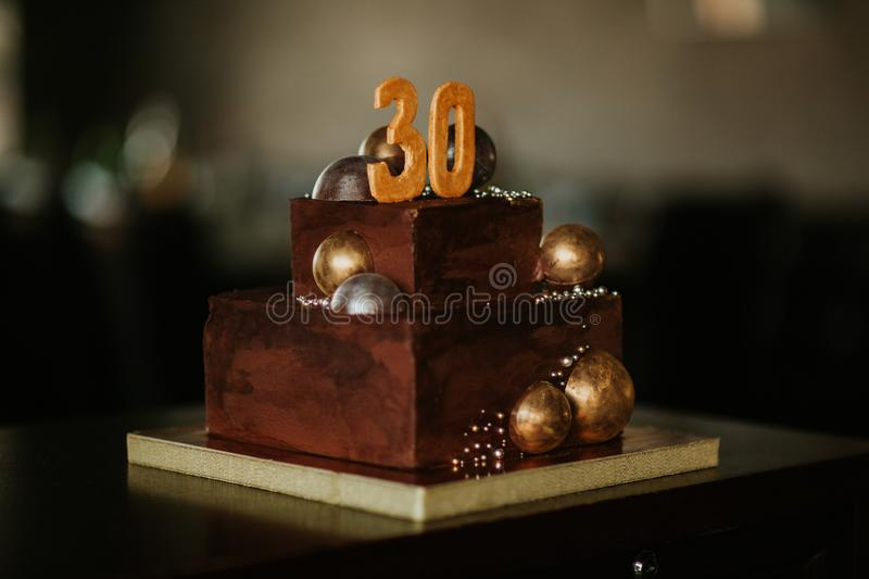 Birthday chocolate cake with a number thirty. decorated with golden chocolate balls. Happy birthday stock photos