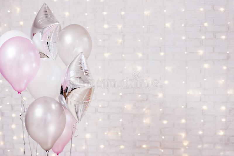Birthday and christmas concept - close up of air balloons over brick wall background with lights. Birthday and christmas concept - close up of colorful air stock photography