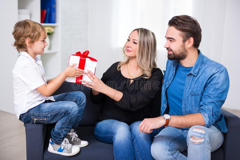 Birthday or christmas concept - couple giving gift to little son royalty free stock image
