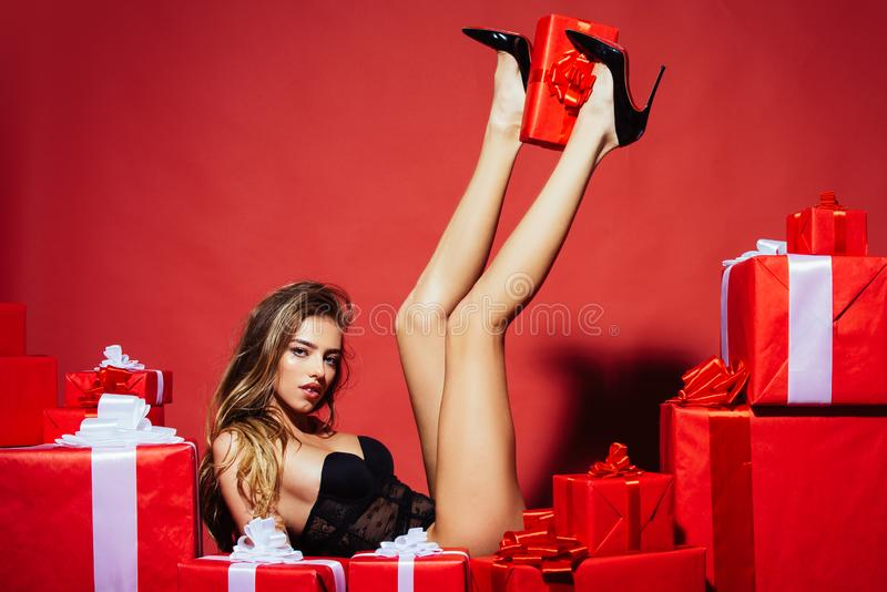 Birthday. Christmas holidays composition with gift boxes and sexy woman on red background. Valentines day. Sexy legs royalty free stock photos