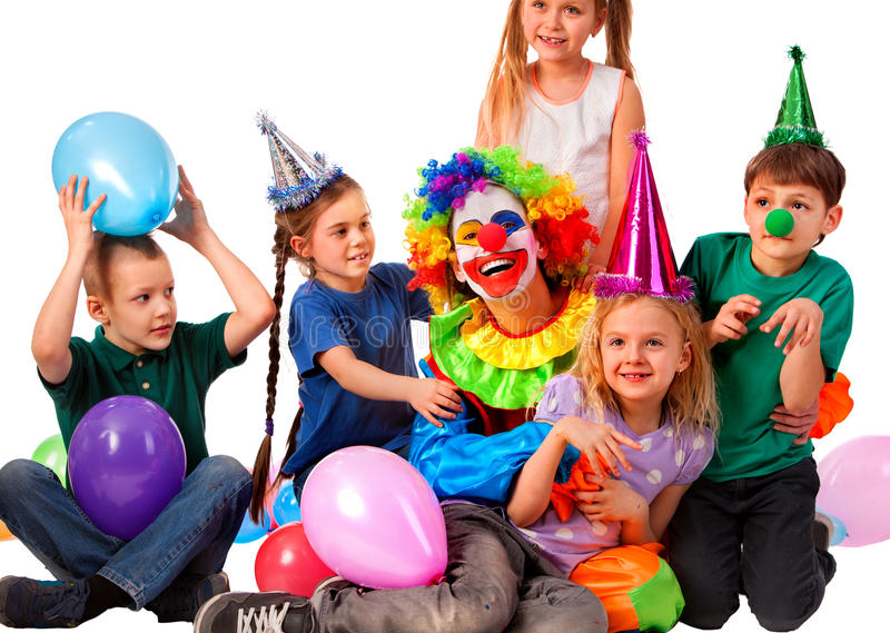 Birthday clown playing children. Kid wearing party hat hold balloons . stock photos