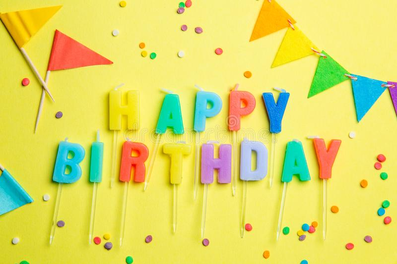 Birthday concept - candles with letters `happy birthday` and confetti royalty free stock photos