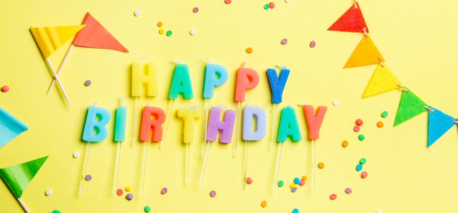 Birthday concept - candles with letters `happy birthday` and confetti royalty free stock photo