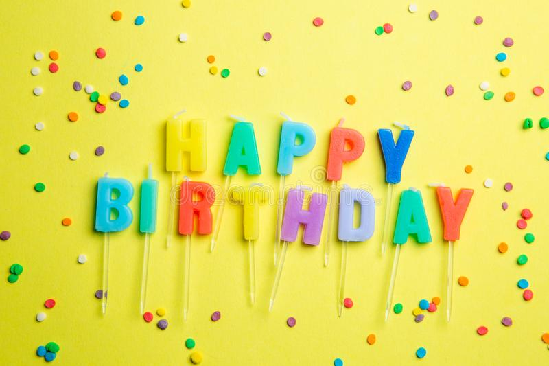 Birthday concept - candles with letters `happy birthday` and confetti stock image
