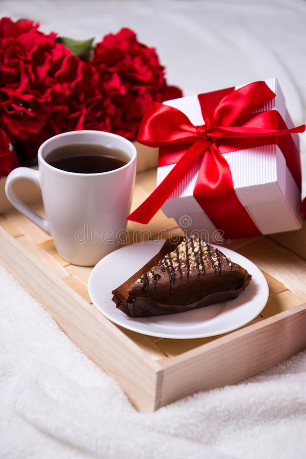 birthday concept - close up of breakfast with cake, tea and little gift on wooden tray stock photo