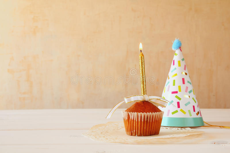 Birthday concept with cupcake and candle, party hat. On wooden table royalty free stock photos