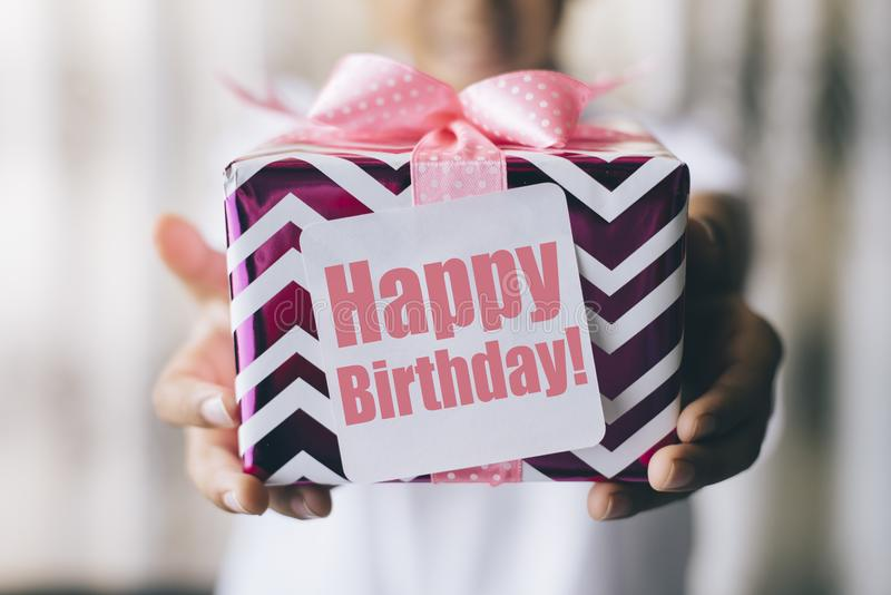 Birthday gift. Birthday concept - young boy holding decorated gift box / present with ` happy birthday ` note stock photos