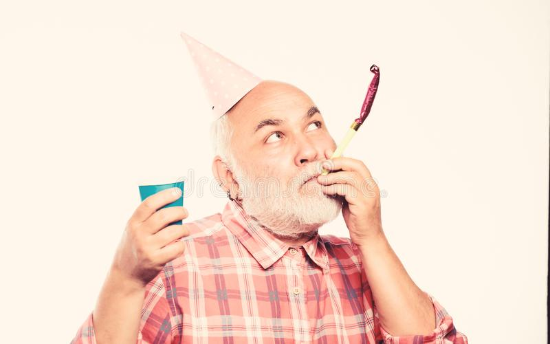 Birthday crazy party. Ideas seniors birthday celebrations. Elderly people. Man bearded grandpa with birthday cap and. Drink cup. Grandfather graybeard blowing royalty free stock photo