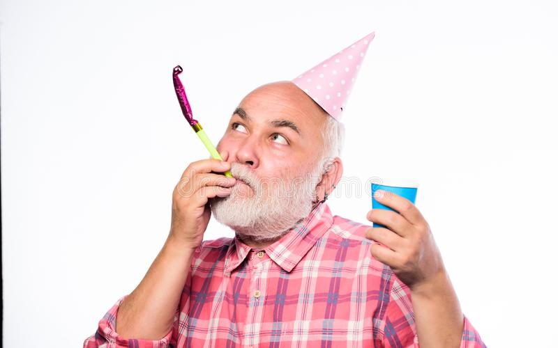 Birthday crazy party. Ideas seniors birthday celebrations. Elderly people. Man bearded grandpa with birthday cap and. Drink cup. Grandfather graybeard blowing royalty free stock photography