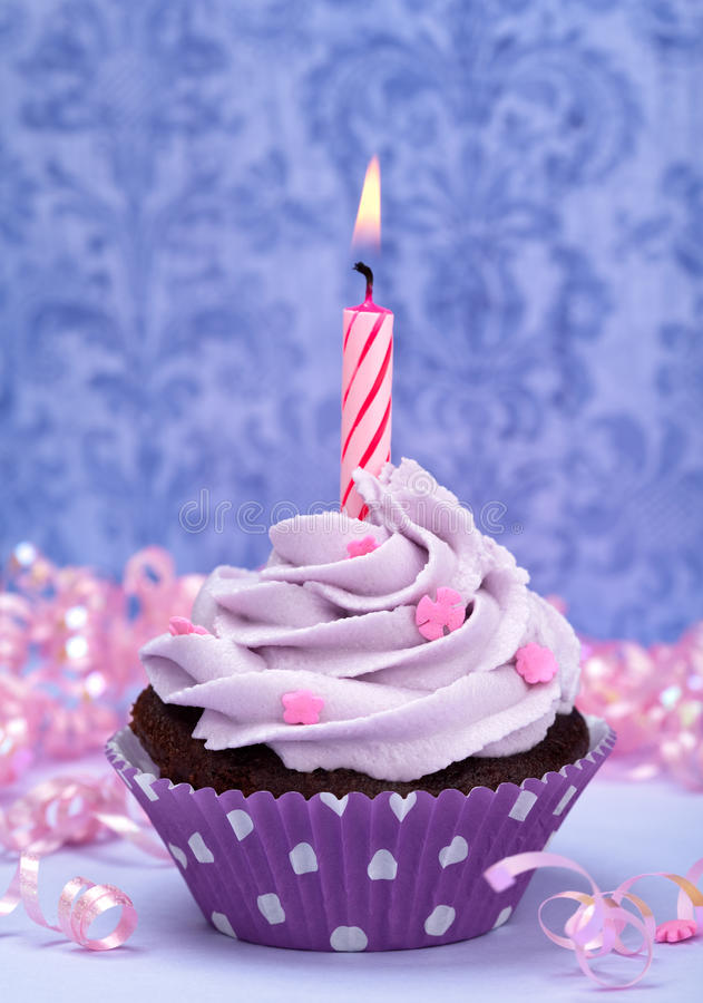 Birthday Cupcake. A birthday cup cake with purple icing, pink sprinkles and a lit birthday candle. Make a wish stock image