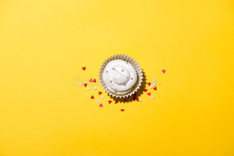 Birthday cupcake against a yellow background royalty free stock photos