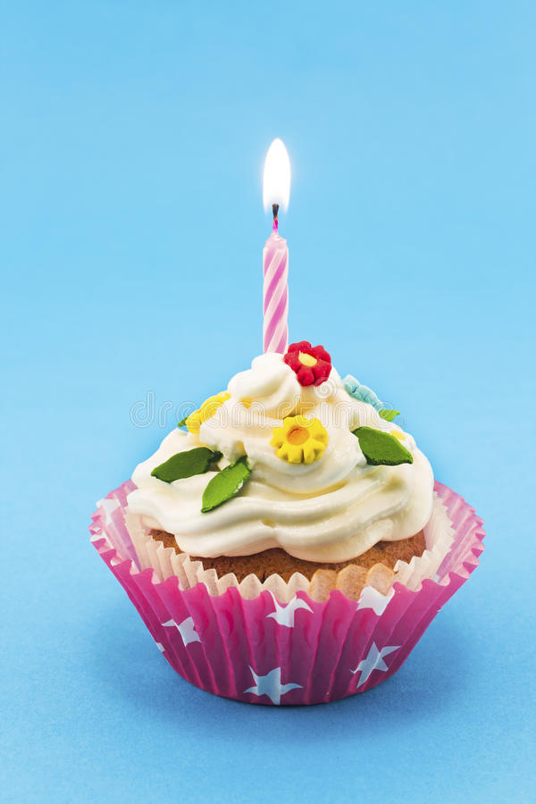 Birthday cupcake on blue background royalty free stock photos