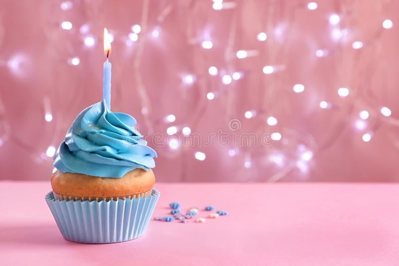 Birthday cupcake with burning candle on table. Against blurred lights royalty free stock photos