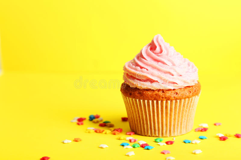 Birthday cupcake with butter cream on yellow background. Birthday cupcake with a butter cream on yellow background stock photography