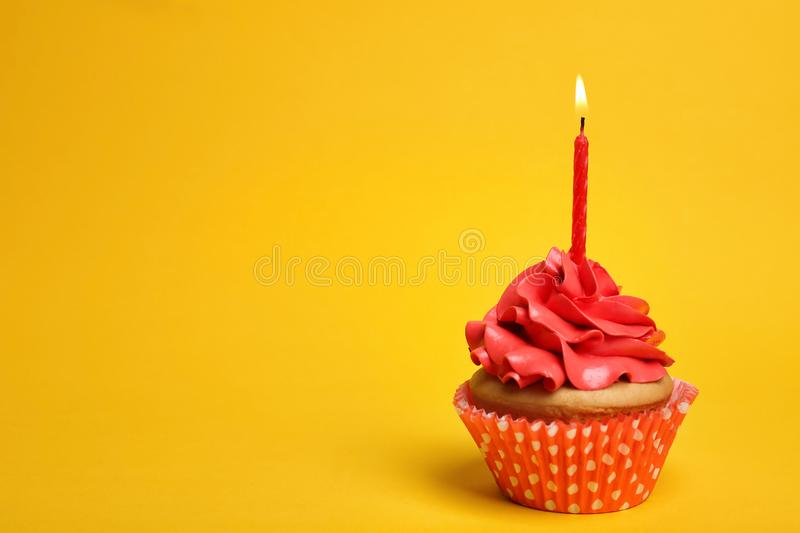 Birthday cupcake with candle. On color background royalty free stock photo