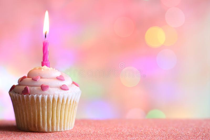 Birthday cupcake and candle on colorful defocused background party concept. Closeup stock photos