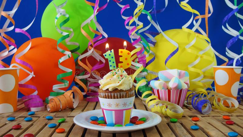 Birthday 13 cupcake with candles burning on rustic wooden table stock photo