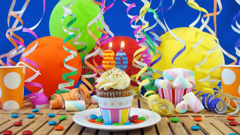 Birthday 80 cupcake with candles burning on rustic wooden table royalty free stock photo