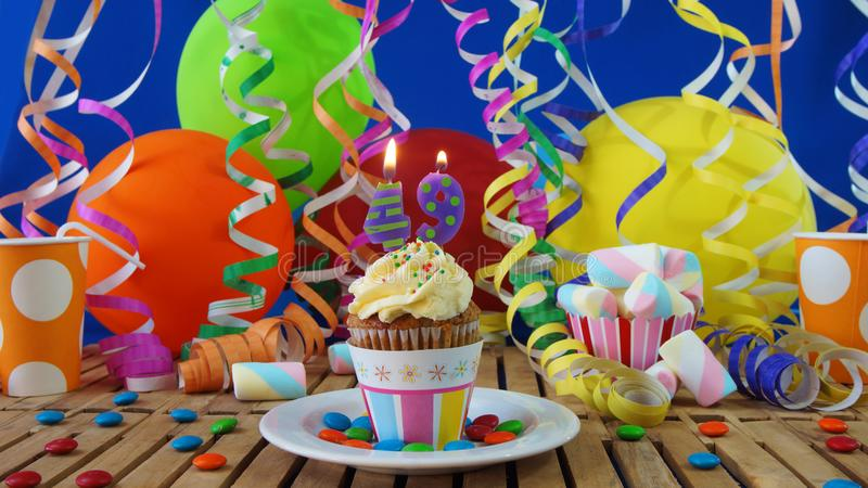 Birthday 49 cupcake with candles burning on rustic wooden table. With background of colorful balloons, plastic cups and candies with blue wall in the background stock photo