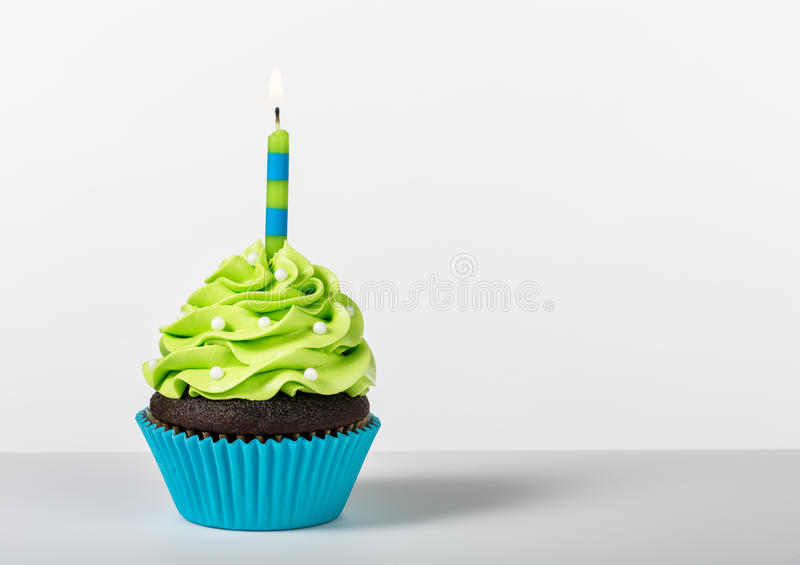Birthday Cupcake. Chocolate Cupcake decorated with green icing, sprinkles and a lit birthday candle on a white background royalty free stock photo