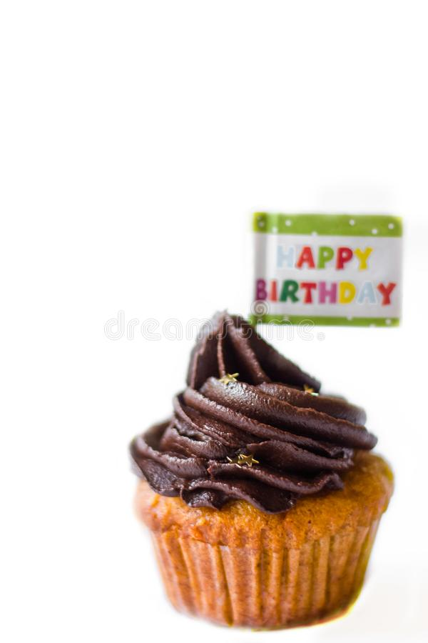 Birthday cupcake with the chocolate frosting on the top. Birthday cupcake with chocolate frosting on the top on the table stock image